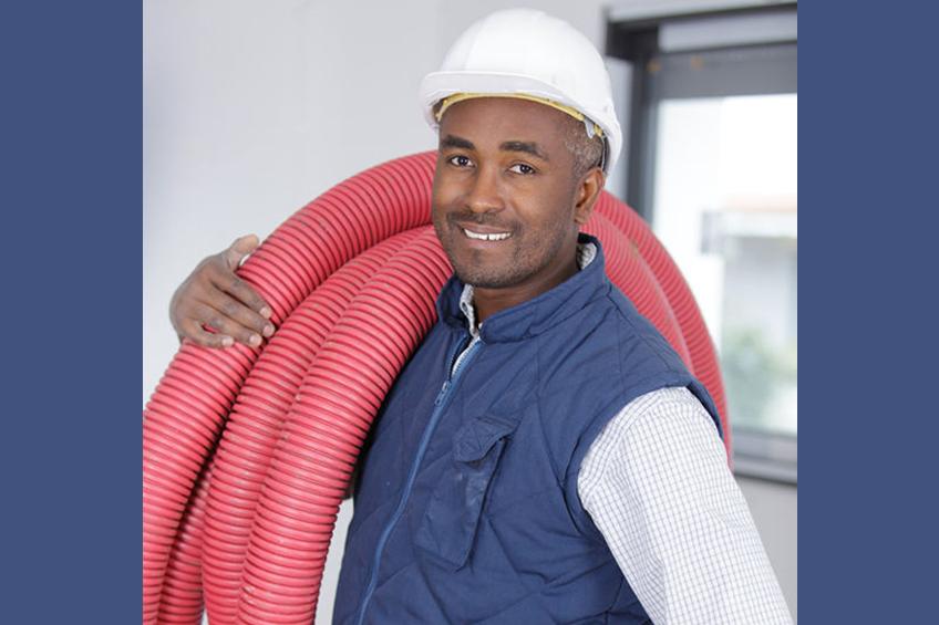 Portrait of smiling female carpenter holding hardhat standing against white background