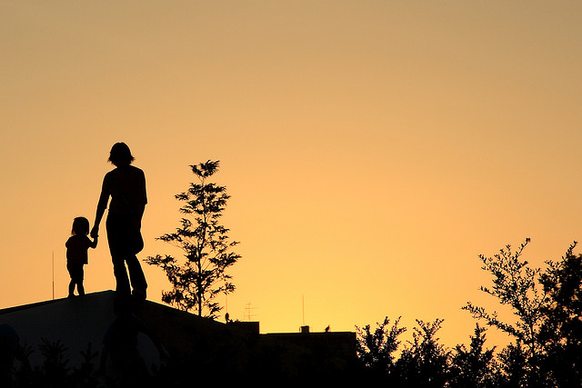 Mother with her daughter standing on the roof in low light sky