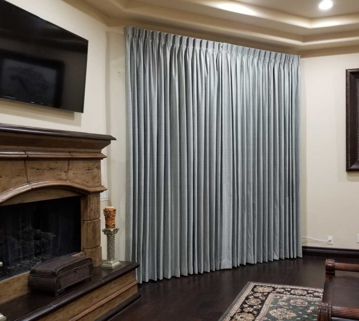 section of a living room with a fireplace and closed drapes
