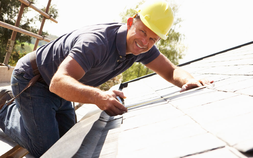 man in hard had performing roof inspection