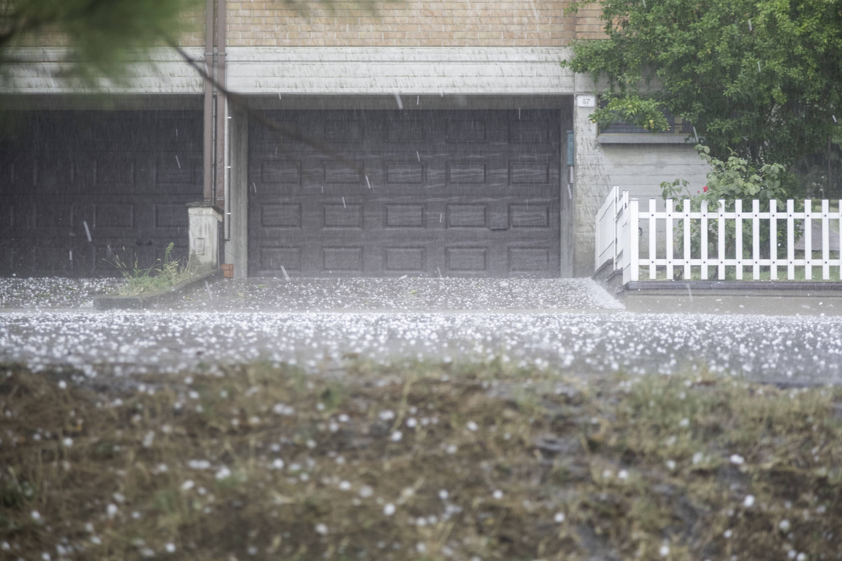 Hail falling from the sky in front of a house
