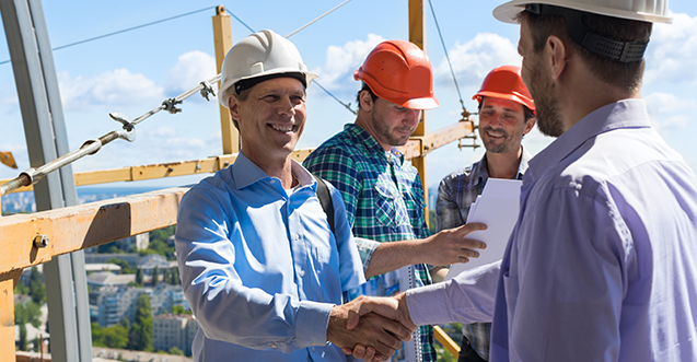Professional roof inspection expert shaking hands with business owner