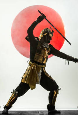 Young man dressed in samurai costume. The young man is posing waving sword. Studio shooting with smoke on black background with a rising red sun at white in a middle of composition