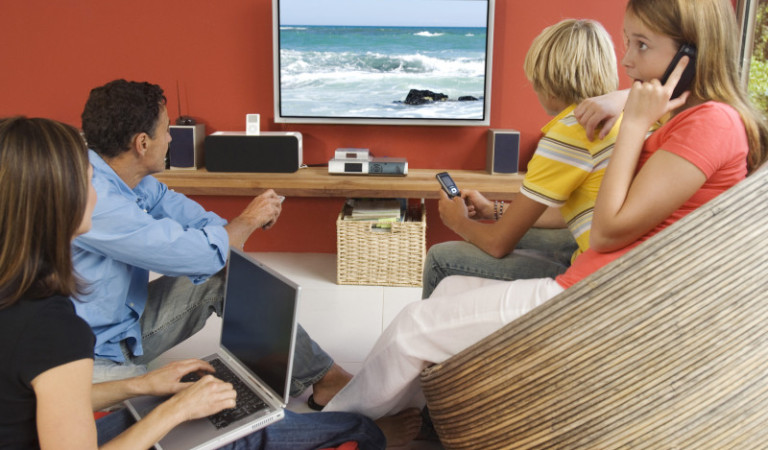 Parents and two teenagers watching television, indoors