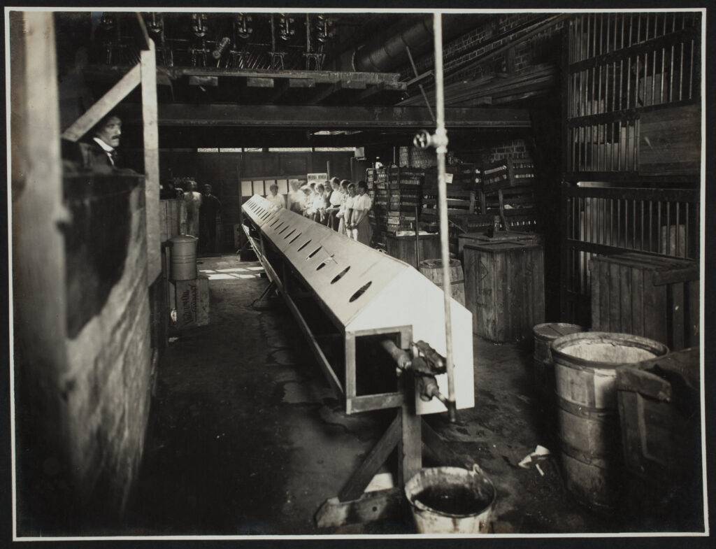 Black and white interior photograph of workers inside a factory. Men and women are shown, with the women lined up on the right hand side of a long piece of equipment with sloping sides and circular holes in it, perhaps containing sinks, with a man looking over a low wall on the left side of the space. The interior is brick, and there is a mezzanine at the back of the space. There are various pipes, buckets, wooden barrels and crates in the space, with glass plate racking on the right hand side.