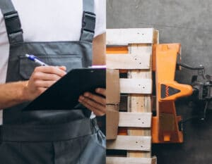 Man with a clipboard reading kamps guide to auditing a pallet supplier
