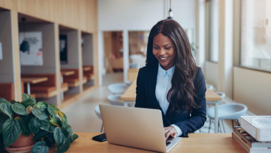 Young African American businesswoman smiling while standing at a table in the lounge of a modern office working on her laptop