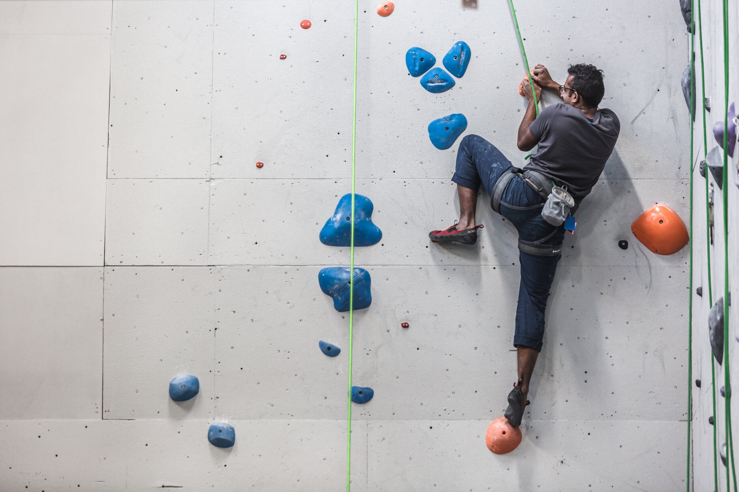 a man scales the side of a rock climbing wall scaled