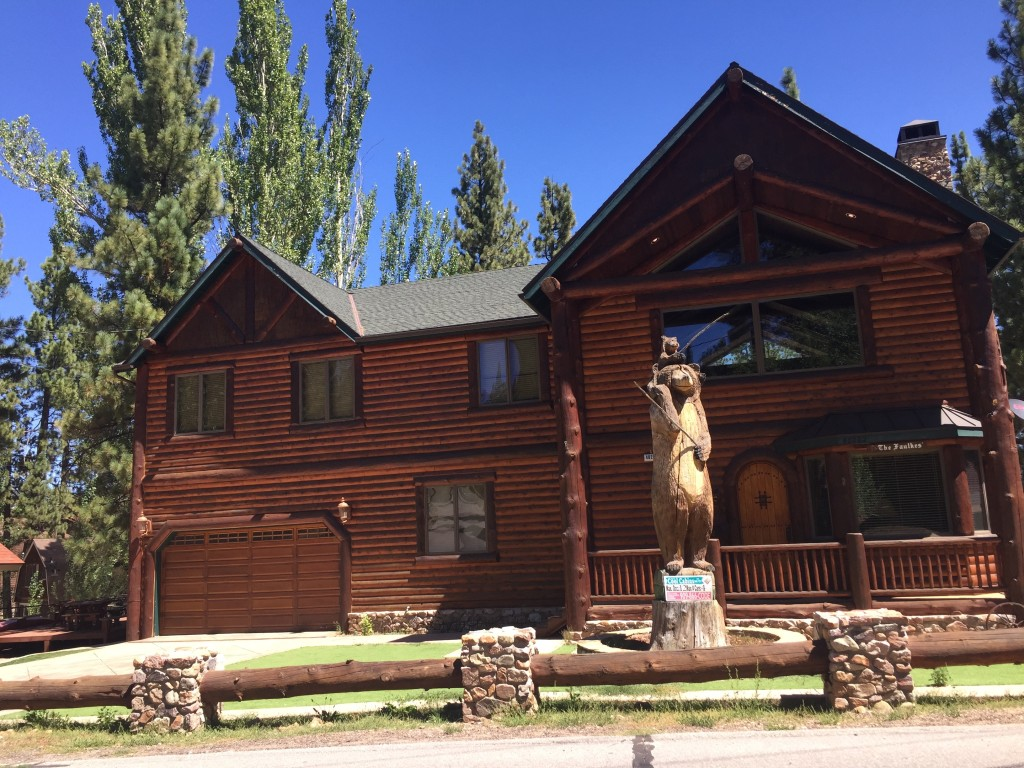 typical log cabin house and wooden bear mascot in Big Bear Lake, California