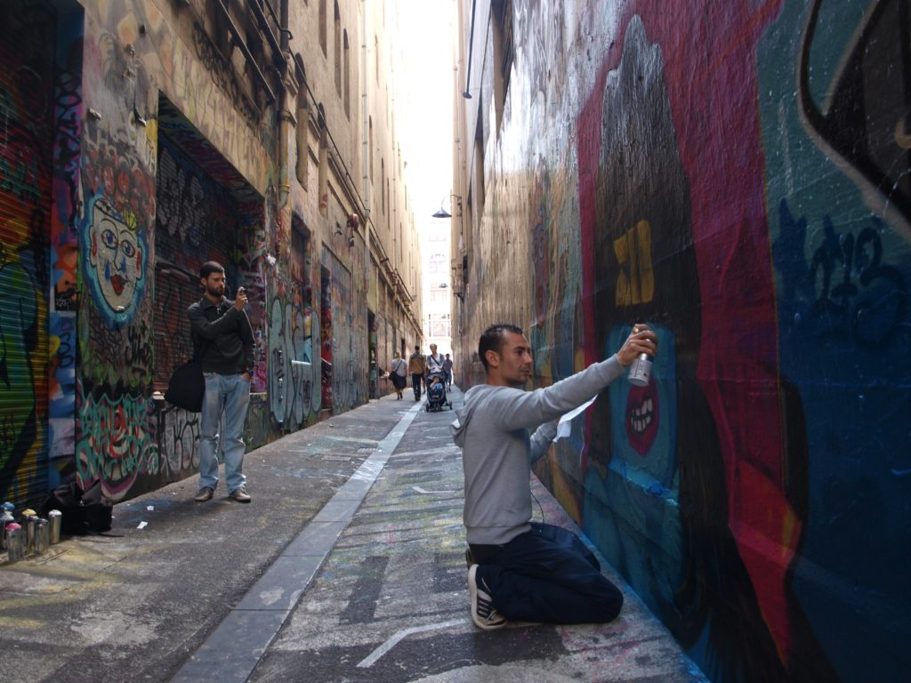 A street artist working on Union Lane in Melbourne