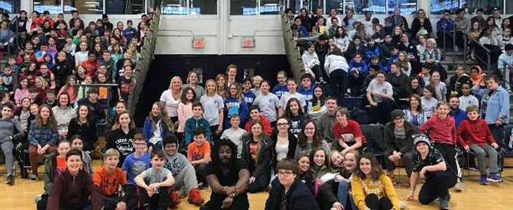 Photo of author Jason Reynolds with happy students behind him
