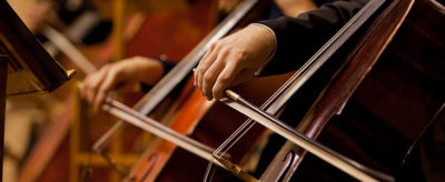 Up close of children playing string instruments