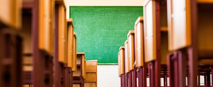 Row between desks looking at a chalkboard