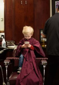 a kid patron sitting in a barber chair playing on his phone