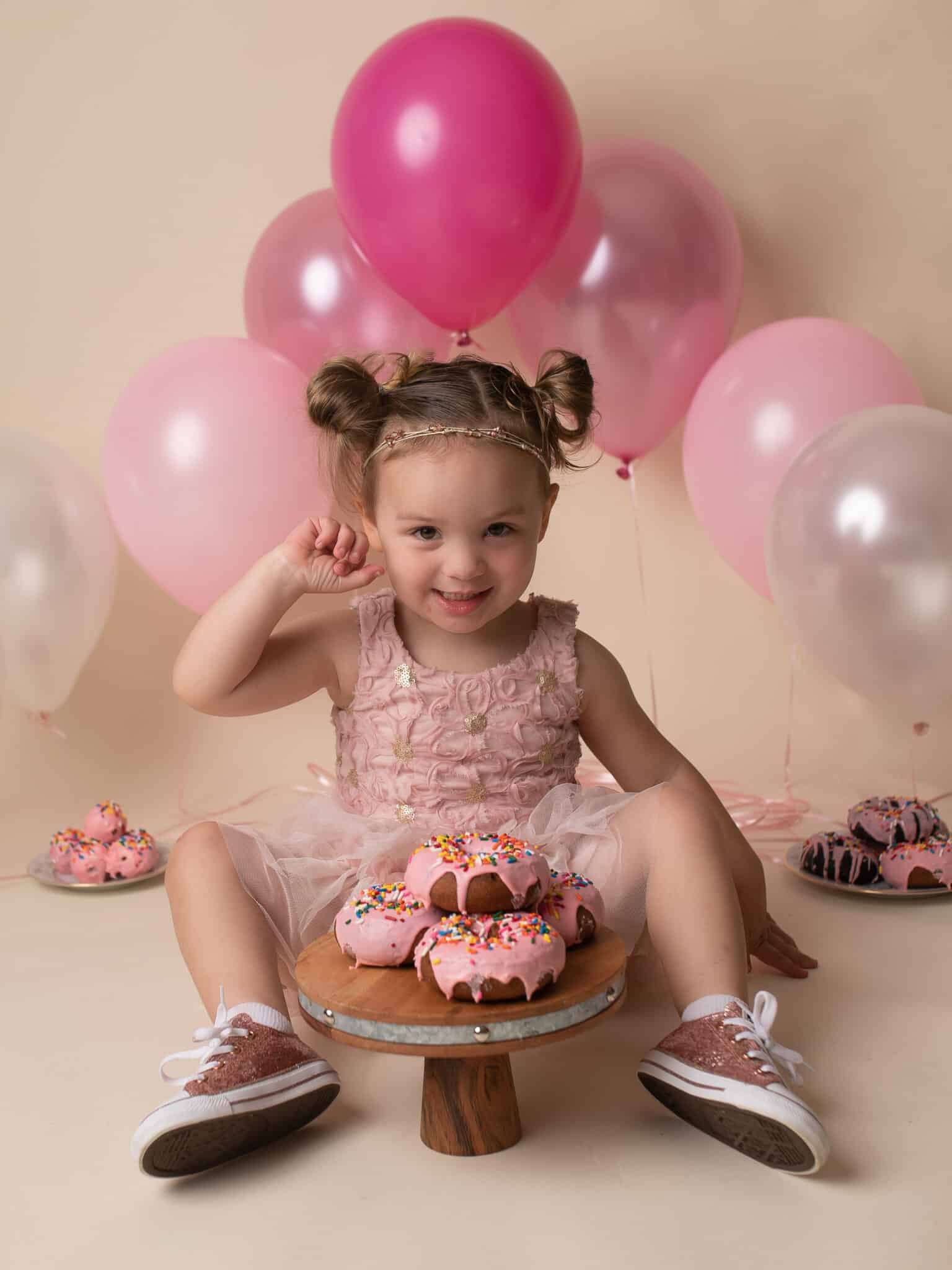 Baby Girl in Pink Dress smiling at the camera with a plate of donuts in front of her.