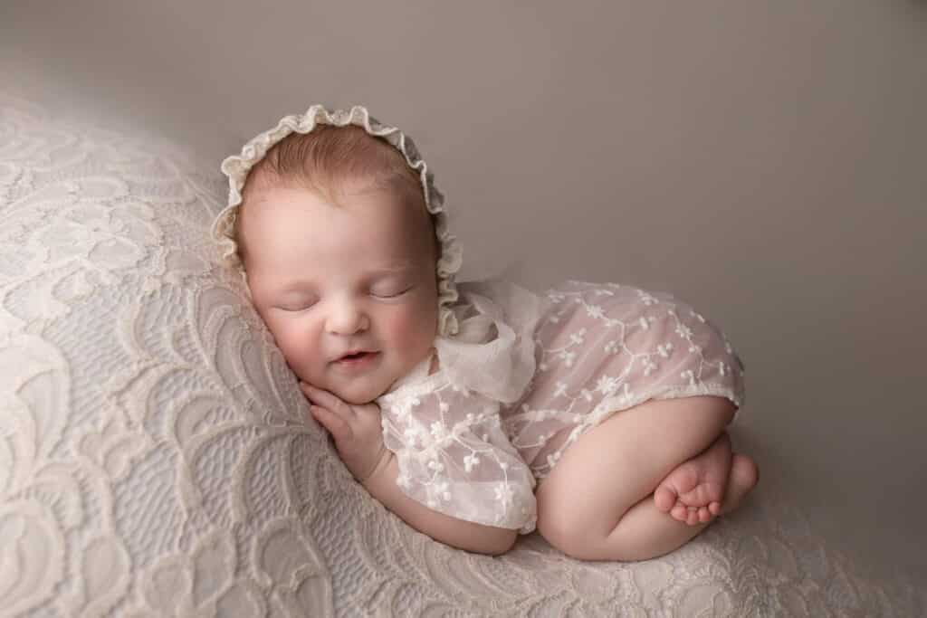 Baby girl smiling in her sleep while wearing a lace bonnet and romper.