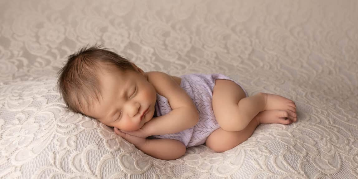 Newborn baby in purple romper sleeping on cream lace.