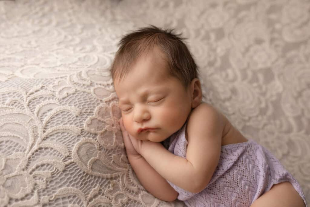 Dark haired newborn girl sleeping in purple romper.