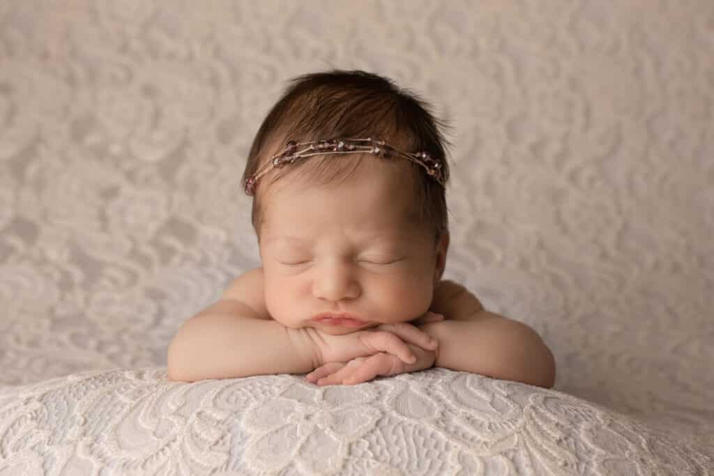 Newborn girl wearing a beaded headband sleeping with her chin on her hands.
