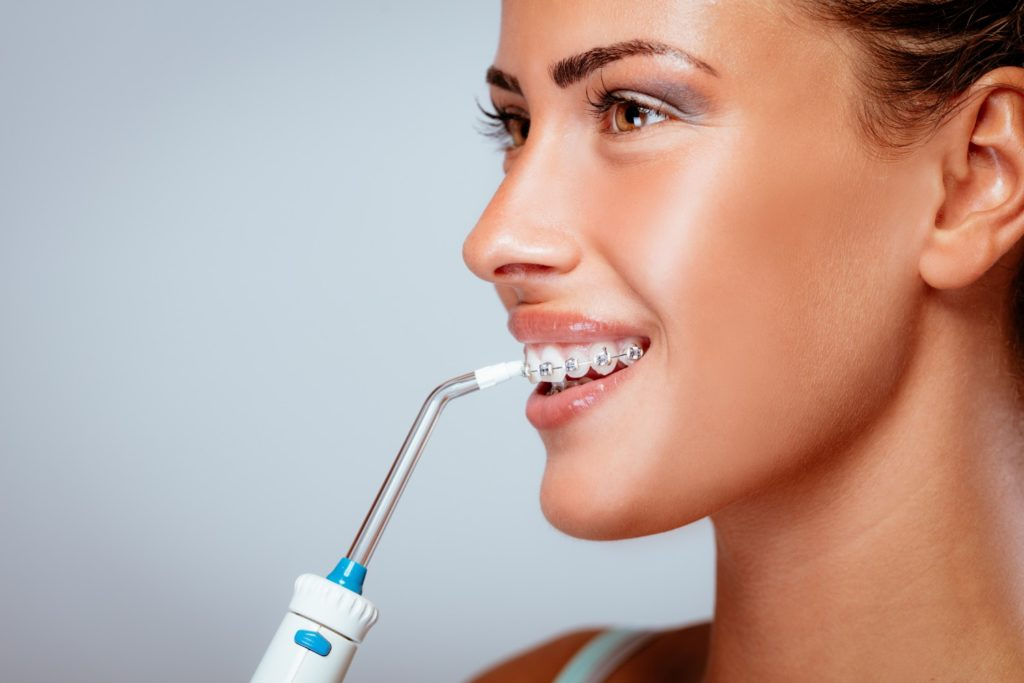 women with braces using water flosser