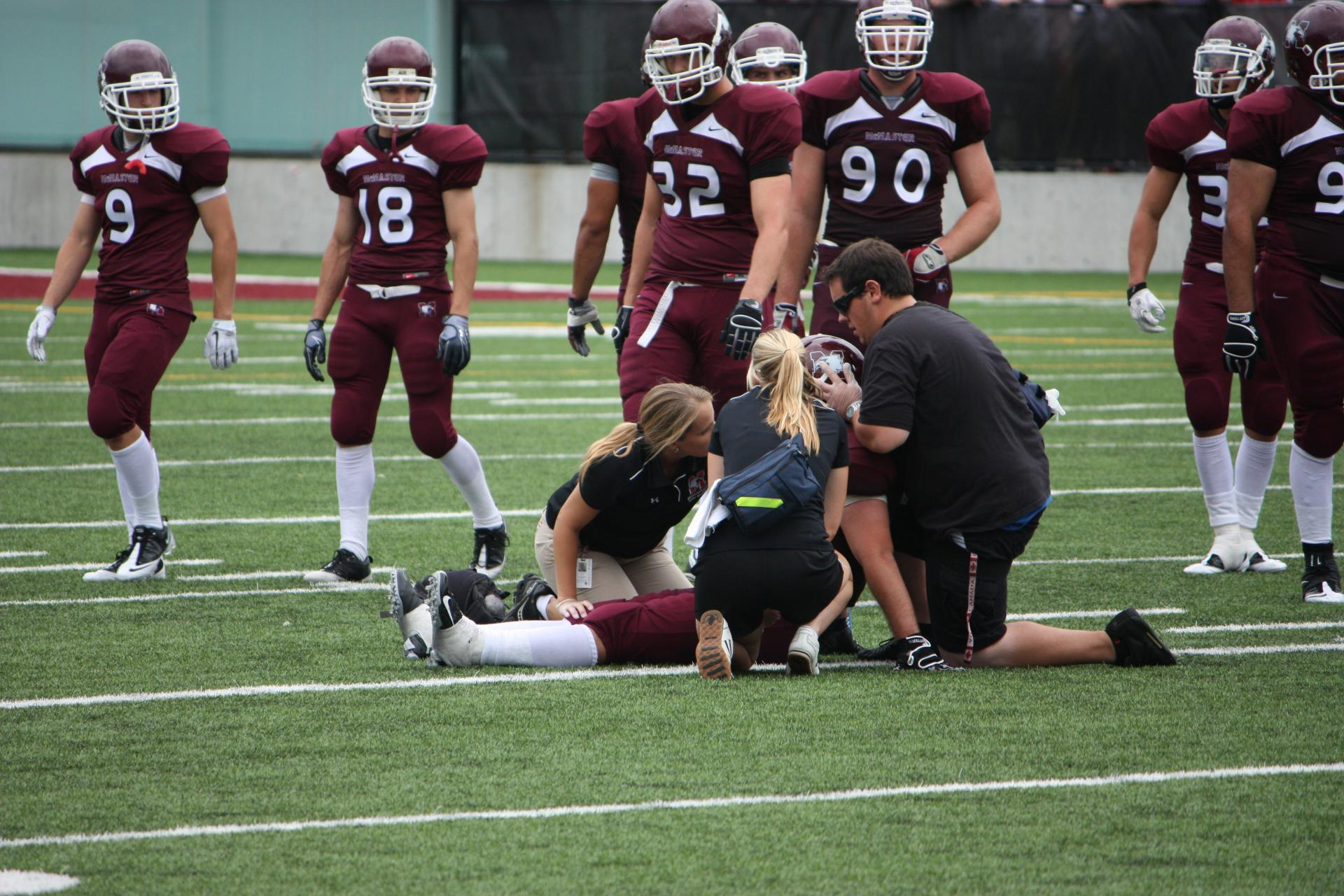 athletic therapist assessing football player on field during a game for sports medicine experts homepage