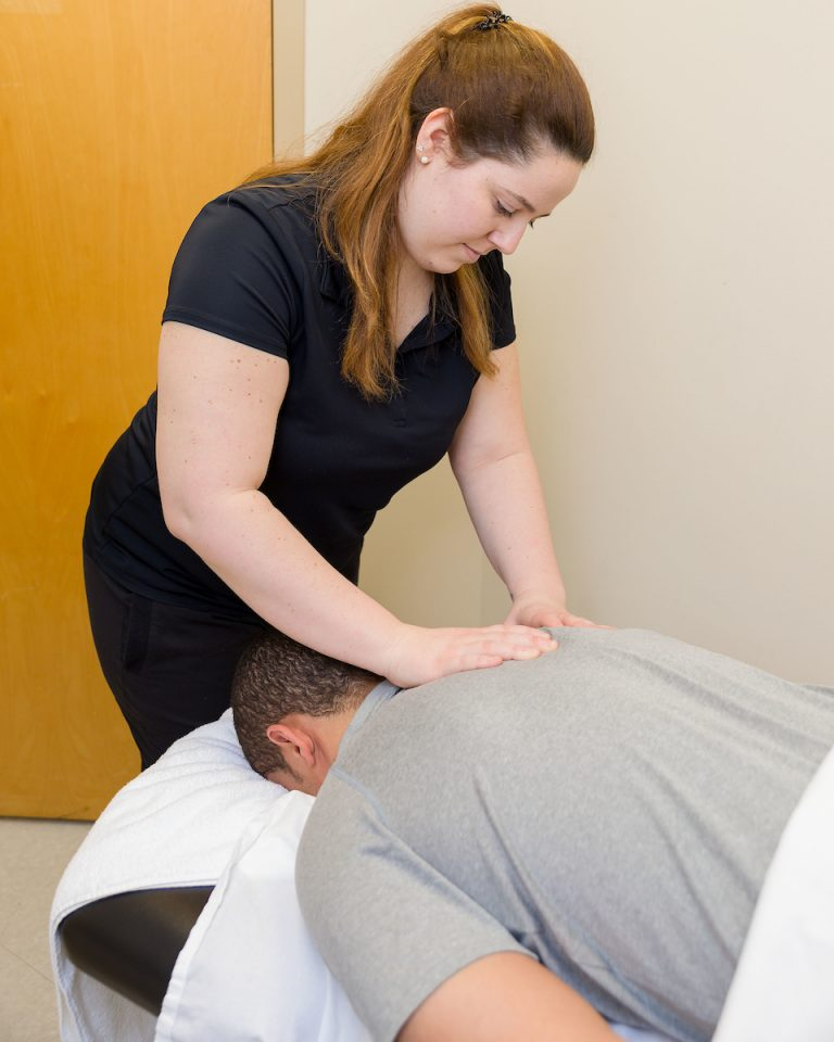 Massage therapist performing massage therapy treatment on patient's back