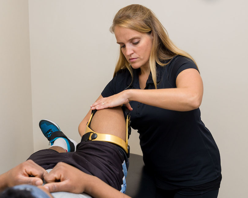 athletic therapist fitting custom knee brace to patient, part of custom knee and hip bracing offered