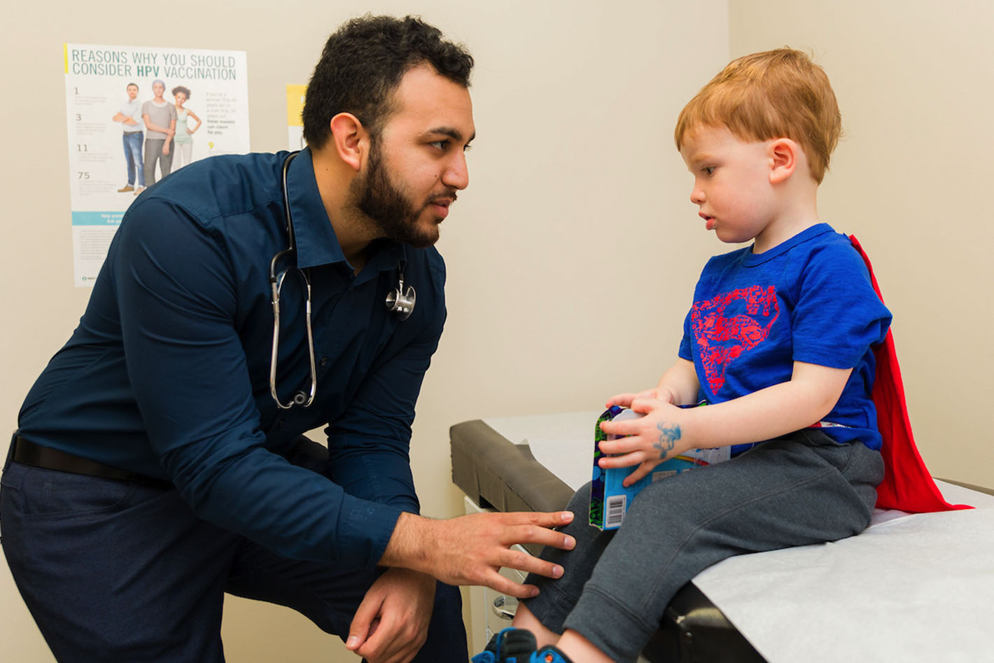 family doctor meeting with child wearing cape