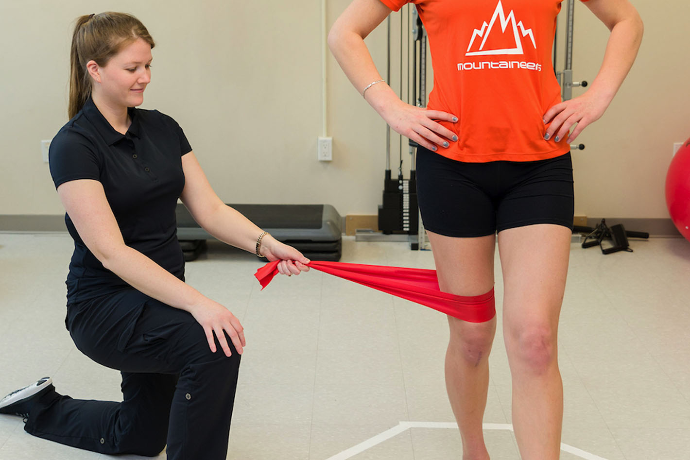 Physiotherapist providing resistance on leg stretch for physiotherapy