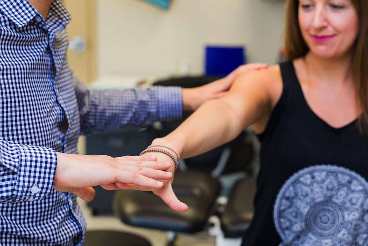 Sports medicine physician assessing patient's arm; medical services thumbnail
