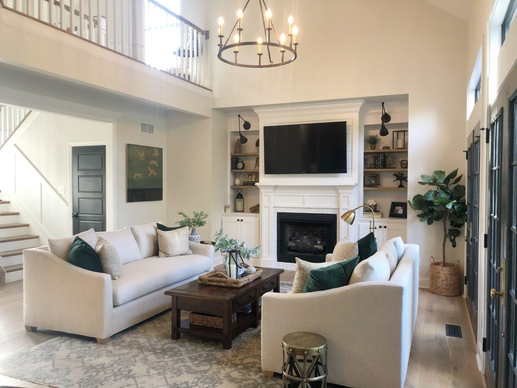 Living room decor with two sofas, area rug and fireplace flanked with builtin bookshelves.