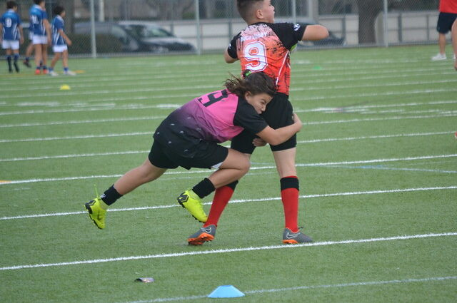 two boys playing rugby. One tackling the other