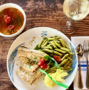 Plate of fish with glass of red wine and soup