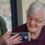 Older woman being shown phone by caregiver