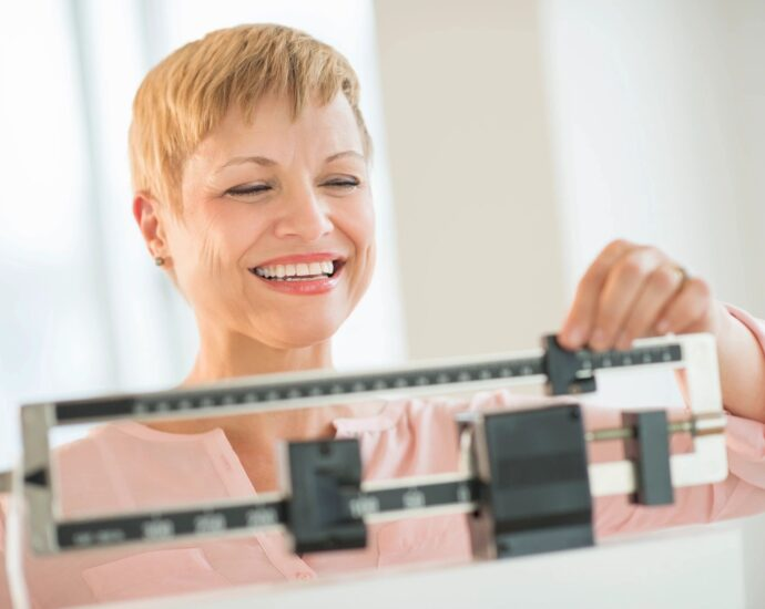 Happy woman on scale, weighing herself