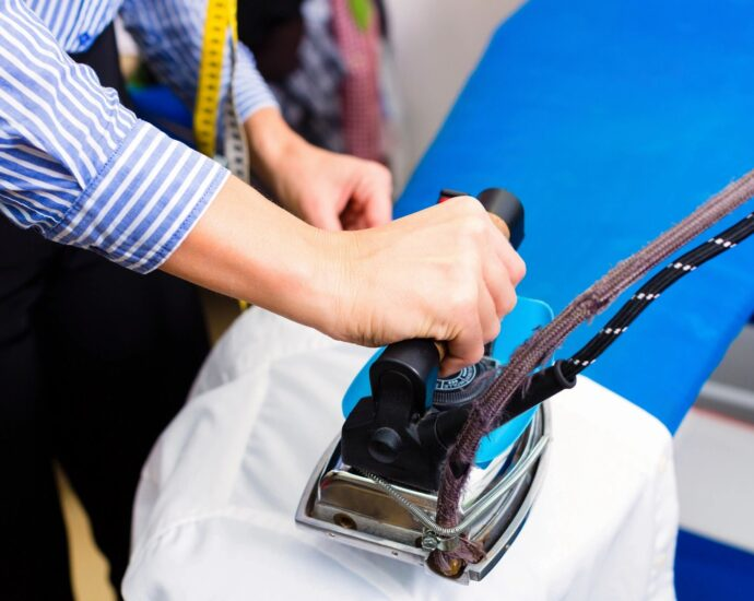 Laborer ironing a shirt at dry cleaner