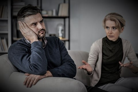 sad and tired husband in the middle of a fight with a cheating wife