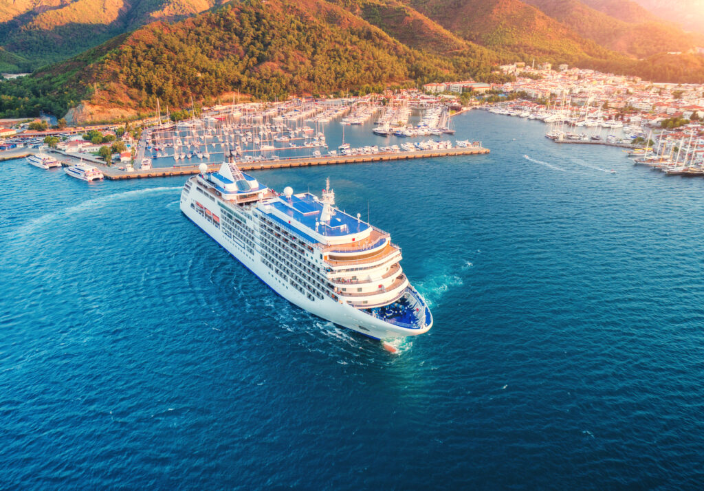 Cruise ship at harbor. Aerial view of beautiful large white ship at sunset. Landscape with boats, mountains, sea, blue sky. Top view of yacht. Luxury cruise. Floating liner in Europe. Travel. Resort