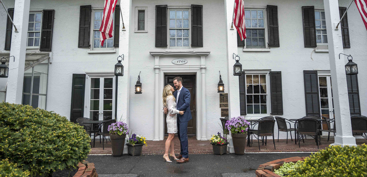 photo of couple embracing in front of Beekman Arms