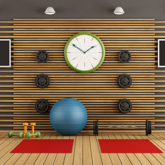 Empty gym with clock on center wall between fitness mats and gym equipment