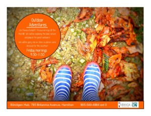 A photo in the first person that shows the ground and all of the colourful fall leaves. There is also a pair of boots that are blue with white stripes.