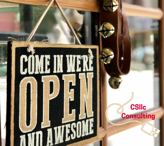 Shop door with Come In We're Open and Awesome sign with a string of bells.