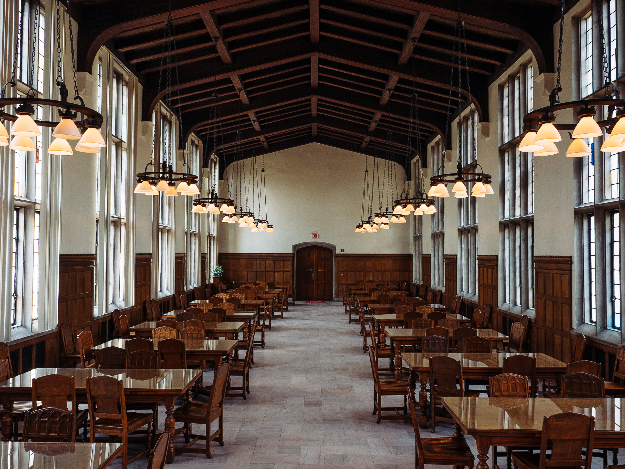long dining hall with historic wooden tables and chairs