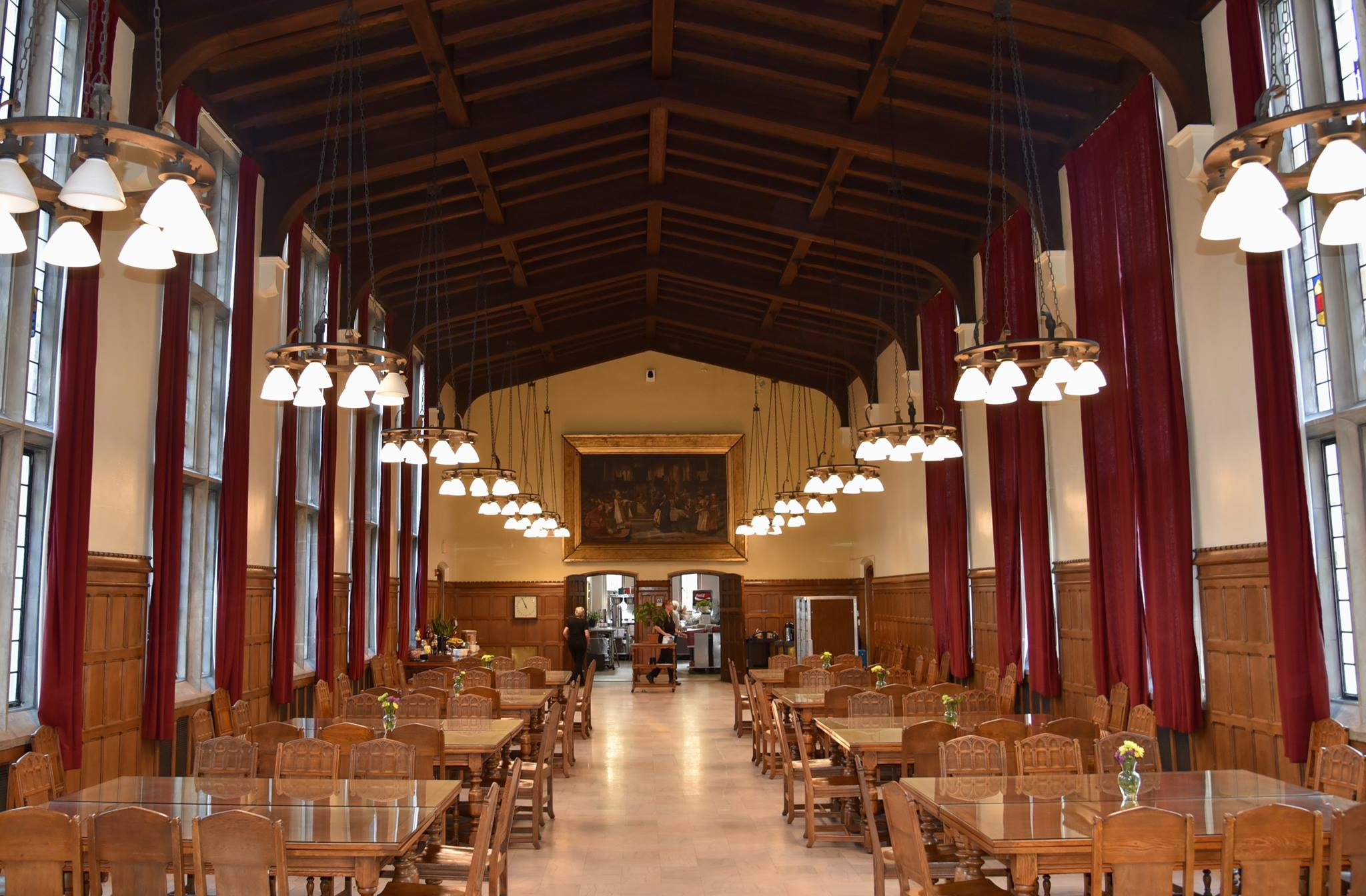 long room with wooden tables and chairs, high ceilings, and red curtains