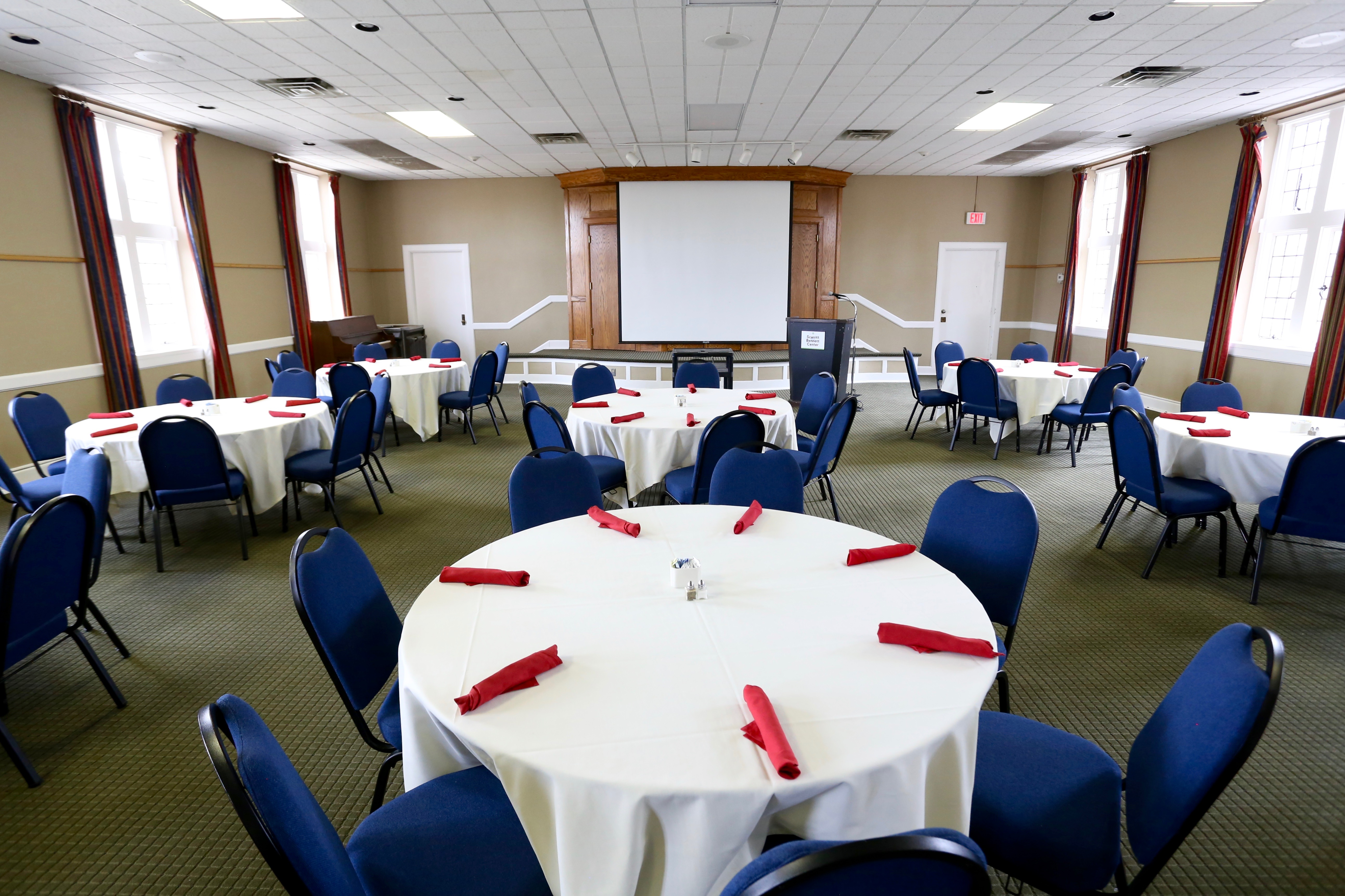 Large room with round tables, stage