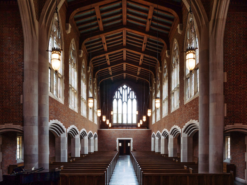 large chapel with rows of wooden pews and high ceilings with wooden beams