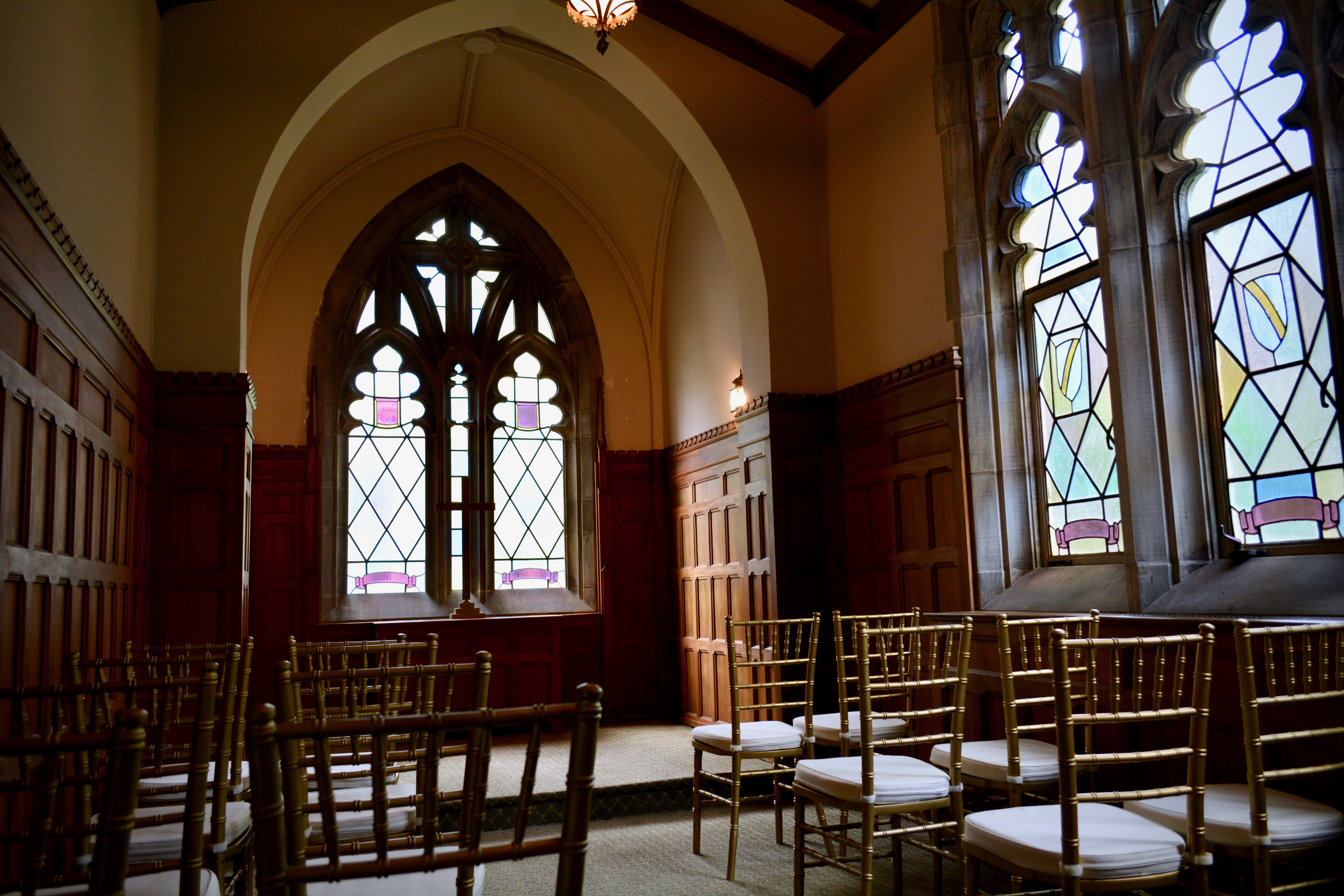 small chapel with stained glass windows and rows of chairs