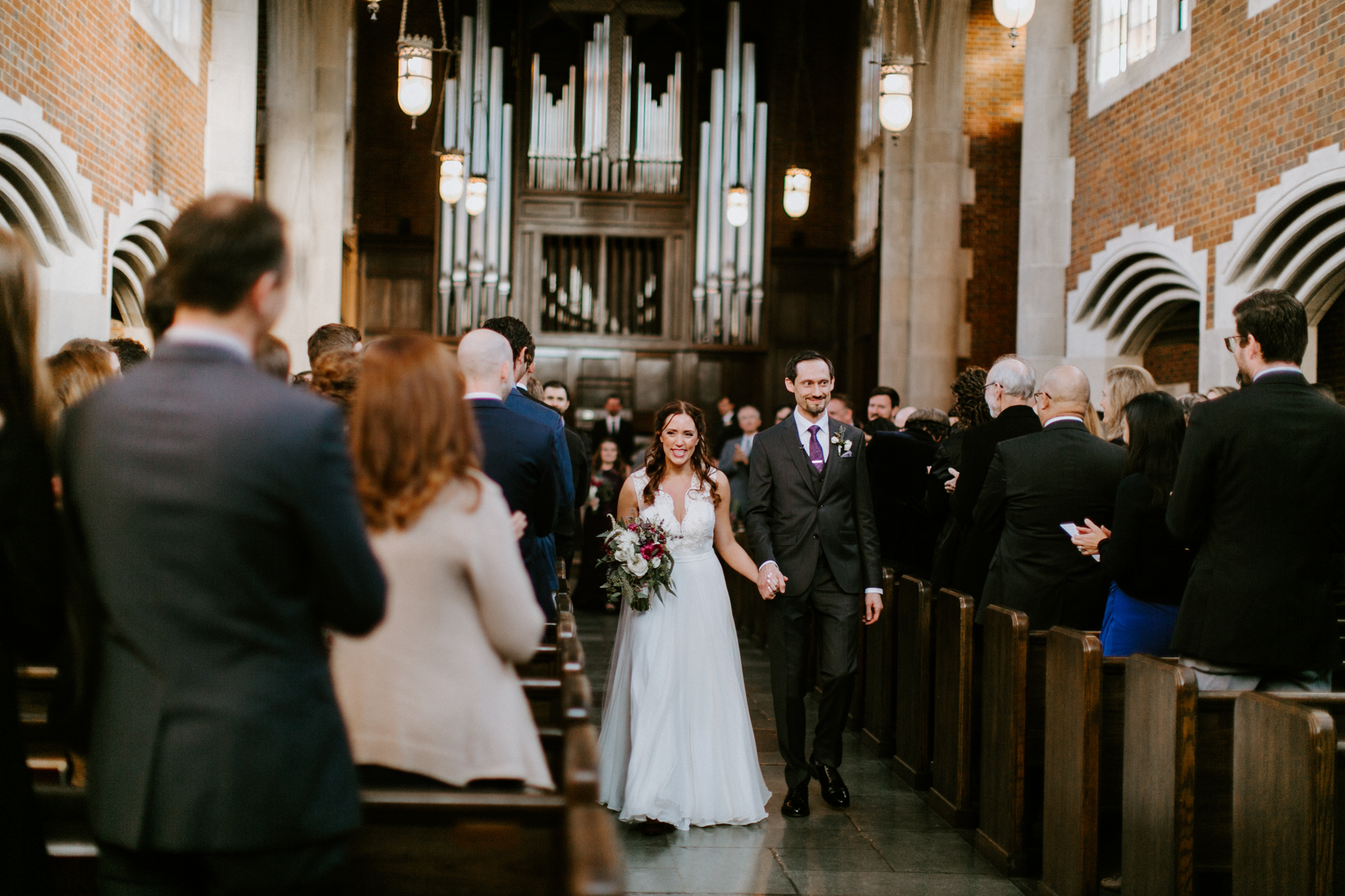 man and woman walking down the aisle at wedding