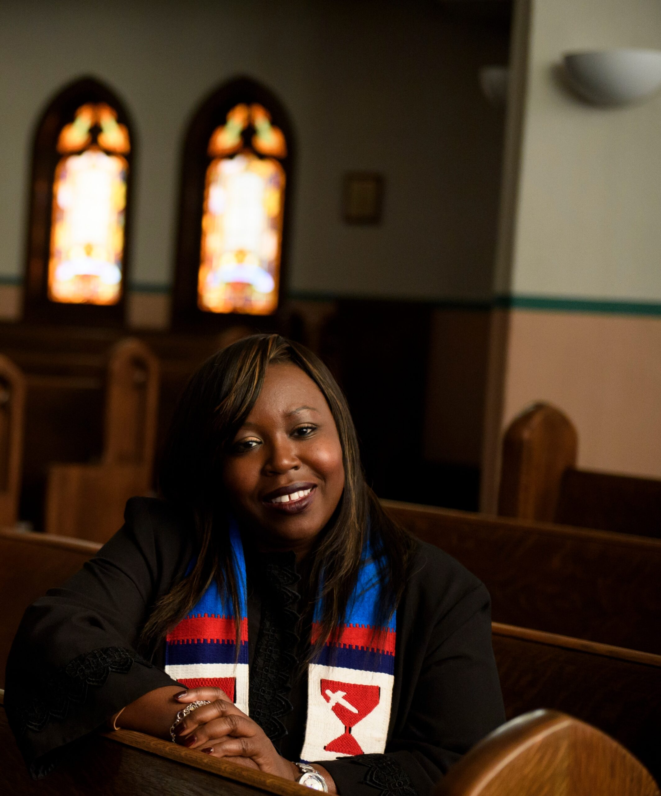 Cherisna smiles at the camera while sitting in church pews