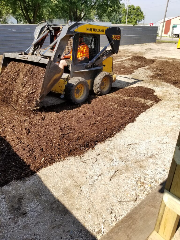 Spreading mulch in entertainment area.